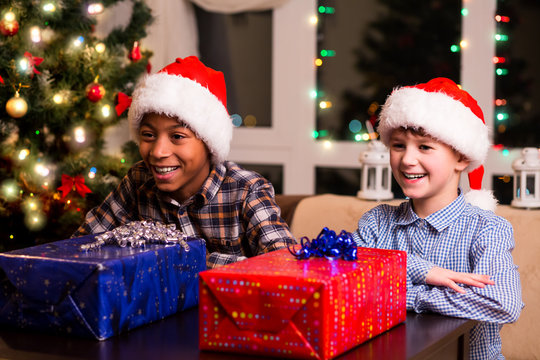 Two boys with Christmas presents. Boys waiting to open presents. It's so hard to wait. Few seconds before joy.