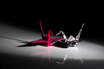 Origami art, colored crane isolated over a black background