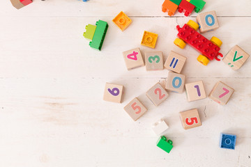 Top view on wooden cubes with numbers and colorful toy bricks on a white wooden background.