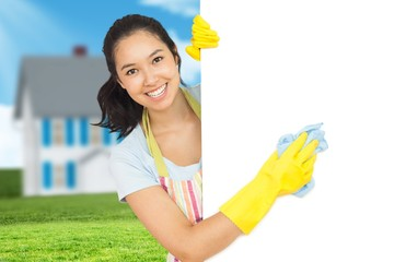 Composite image of cheerful woman cleaning white surface