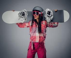 Female holding a snowboard on her shoulder.