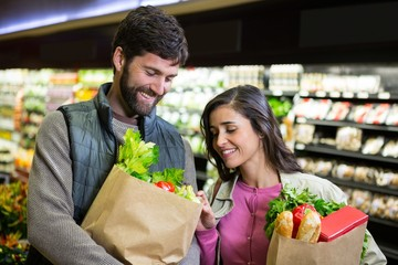 Smiling couple shopping for vegetables in organic section