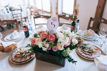 tables decor in the restaurant at wedding ceremony, flowers, food and number table