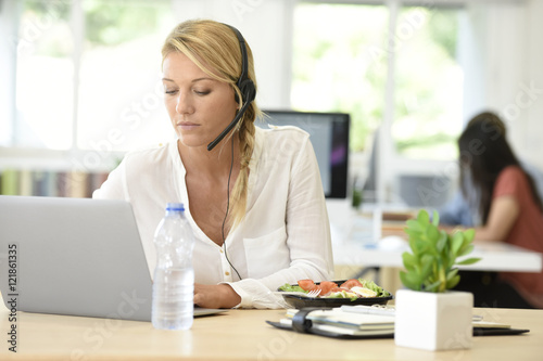 """""""Busy customer service manager eating lunch in office ..."""