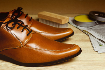 Closeup leather shoes with cleaning sets on wood table