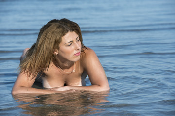 Blond woman wear bottom bikini lying in the sea water and cover her topless nude breast with the hands