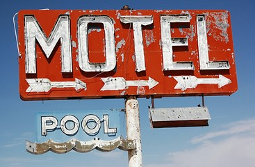 Low Angle View Of Abandoned Motel And Pool Signs Against Sky