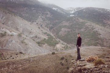 Full Length Of Man Standing On Hill In Front Of Mountains