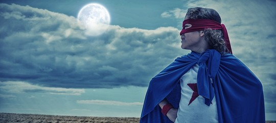 Composite image of boy wearing superhero costume