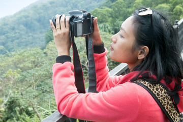 Woman photographs with camera in nature