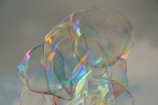 Low Angle View Of Bubbles In Mid-Air Against Cloudy Sky