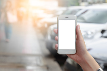 Smartphone isolated white screen in hand with blurred car parking on road