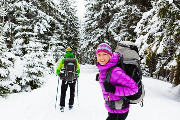 Couple happy hikers trekking in winter woods