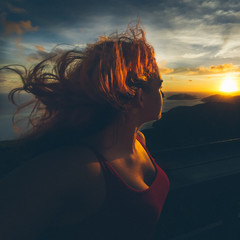 Young Woman With Tousled Hair Looking At Sunset