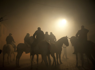 People On Horses Against Smoke On Street
