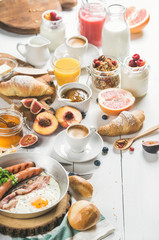 Fried egg with sausages and bacon, bread, croissants with jam and butter, fruits, smoothie, orange juice, yogurt, granola with milk and coffee on white wooden background. Selective focus, copy space