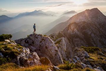 Zelfklevend Fotobehang Bergen Man standing on a mountain summit at sunset