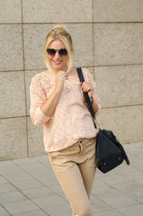 Stylish young blonde smiling, holding shoulder bag, woman fasion