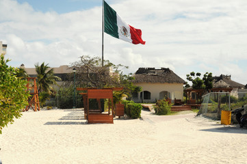 huge Mexican flag on the flagpole on the beach in Cancun