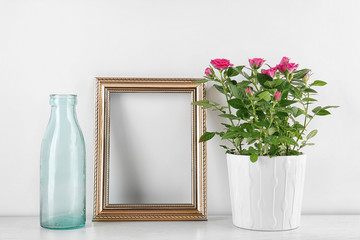 Vase with roses, bottle and photo frame on table