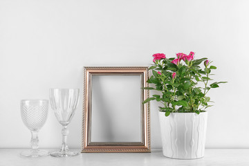 Vase with roses, wine glasses and photo frame on table
