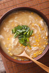 Delicious corn and chicken soup close up in a bowl. vertical top view