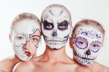 Three girls with Halloween face art on white background
