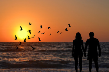 Couple silhouettes holding hands looking at sunrise on the beach
