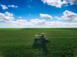 Wall Mural - Tractor mowing green field