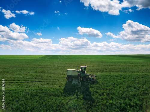 Wall mural Tractor mowing green field