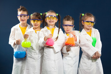 Group happy kids doing science experiments in the laboratory.