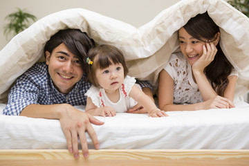 布団の中に潜る家族