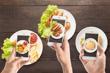 Friends using smartphones to take photos of sausage, pork chop, Fries chicken and burger.