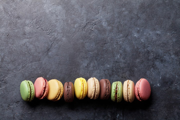 Colorful macaroons on stone table. Sweet macarons
