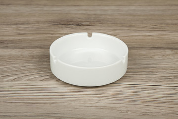 White ceramic ashtray on a wooden background.