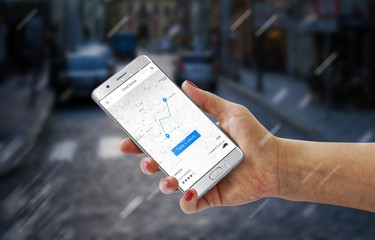Driver hire app on modern smartphone in woman hand. City street in background.