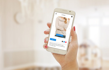 Modern shopping app on smart phone in the women hand. Buying clothes on web site or app.