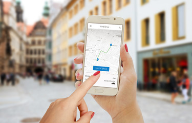 Find drive smartphone app in woman hand. City map, trail, driver and car on phone display.
