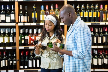 Couple looking at wine bottle in grocery section