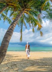 woman under palm sea