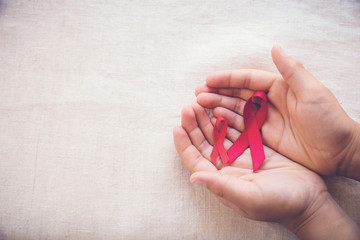 hands holding Red Ribbons on toning background, HIV/AIDS, Anosmi