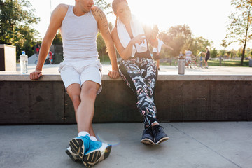 Man and woman in sportswear sitting and chatting