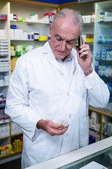 Pharmacist talking on mobile phone while checking medicine