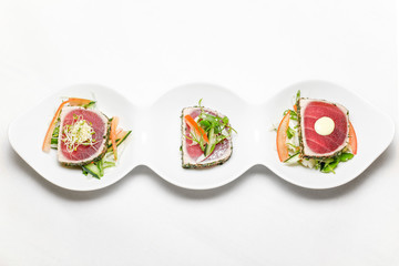 sushi serving-3 pieces of Tuna with chpped vegetables on a white plate, horizontal