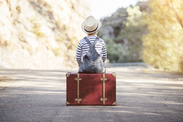 niño con maleta en la carretera