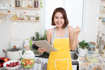 Asian young woman eating healthy food and using a tablet compute