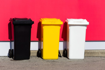 Three colored recycle bins on the street/ Black/ Yellow/ White