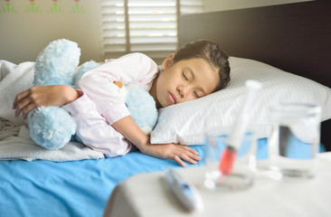 Generic liquid medicine syringe in glass on table in front of sleeping child for health and illness concept, young Asian girl hugs the blue teddy bear. selective focus on face.
