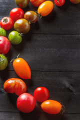 Colorful ripe tomatoes. Delicious vegetarian food. Dark backgrou
