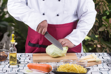 Chef cutting cabbage on wooden broad
